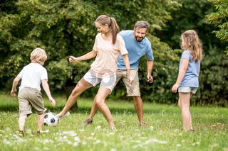Mutter spielt Fußball mit Familie