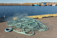 Green fishing net at the harbor with blue sea and fishing boats unfocused in the background, Lista in Norway