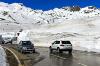 Cars driving on the pass road between high snow walls acCars drross the St Gotthard Pass,Switzerland