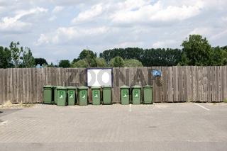 Grüne Müllcontainer vor Bretterzaun