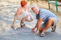 Verliebter Senior malt Herz auf den Boden