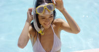 Smiling woman in swim suit wears goggles