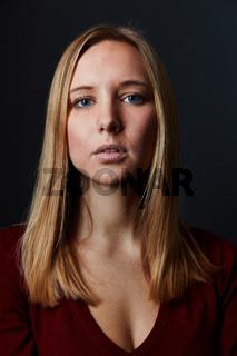 Junge blonde attraktive Frau schaut ernst