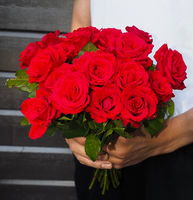 Male person holding a beautiful bouquet of red roses
