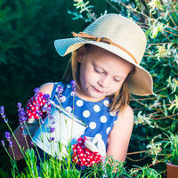 Cute girl watering herbs. Child taking care of plants. Kid with water can. Little gardener with lavender and rosemary.