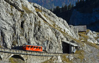 Red railcar of the Pilatus Railway in a steep passage in the Pilatus massif, Alpnachstad,Switzerland