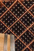 Several Varietal Wine Bottles and Barrel Age Inside Cellar