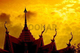 Dramatic sunset with buddhist temple silhouette
