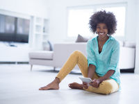 black women using tablet computer on the floor at home