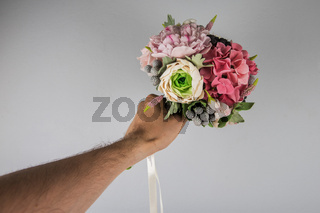 male hand giving wedding bouquet