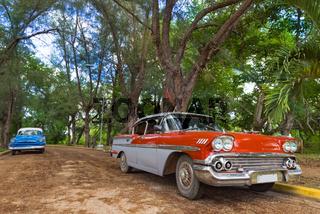 Rot weisser amerikanischer Oldtimer parkt in Santa Clara Kuba - Serie Cuba Reportage