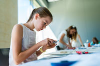 Young girl on the course of architectural design for children - preparing architectural model