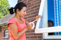 Woman sticking adhesive tape on window glass