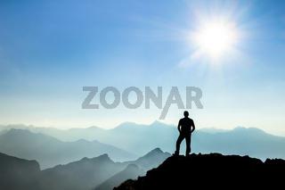 Man reaching summit enjoying freedom and watching towards mountain ranges.