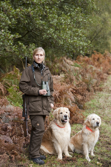 Huntress with dogs in hunting preserve