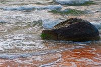 Small sea waves breaking on a rock