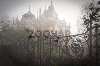 Alte Villa mit Eisenzaun im Morgennebel