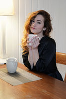 young woman in dressing gown drinking cup of coffee sitting at kitchen table