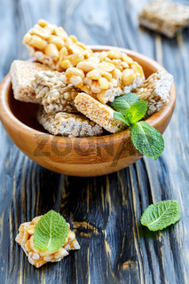 Bowl of honey bars with peanuts, sesame seeds and sunflower seeds.