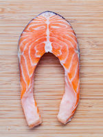 Fresh salmon fillet sliced flat lay on bamboo cutting board. Fresh salmon fillet sliced tempts buyers at fresh seafood stall.