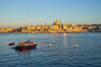 A yacht moored in the Marsamxett harbor with the Valletta capital city on the background. Malta