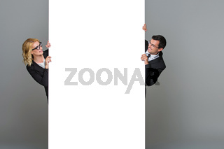 Businessman and business woman with big empty poster