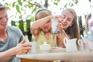 Mädchen schüttet Puderzucker auf Kuchen