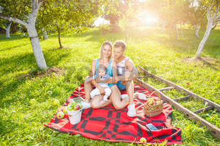 Happy family enjoying a picnic with their baby outdoors
