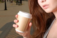 Depressed woman with takeaway coffee cup in hands part of the face shot