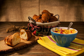 Continental breakfast with cornflakes and strawberries in a cup of milk and croissant