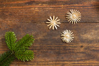 Fir branch with stars arranged on weathered wooden board