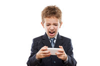 Smiling child boy in business suit playing games or surfing internet on smartphone computer