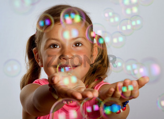 Young girl catching bubbles