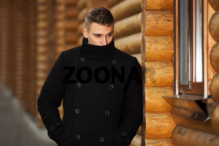Young handsome man in classic black coat standing at the wooden wall