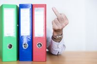 An official shows a stinkfinger behind his file folders