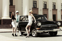 Young fashionable people at the retro car