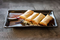 Fried spring rolls on black plate