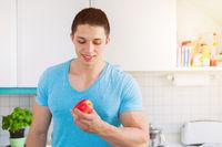 Gesunde Ernährung junger Mann Essen Apfel Frucht Obst in der Küche Textfreiraum