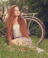 Beautiful smiling girl sitting next to bike on fresh grass with her face looking up toned image