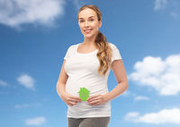 happy pregnant woman with green house