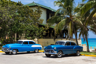 Amerikanischer blaue Oldtimer parken am Strand unter Palmen in Varadero Cuba - Serie Cuba Reportage