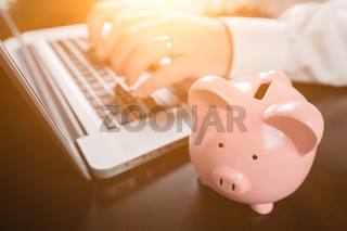 Piggy Bank Near Male Hands Typing on Laptop Computer.