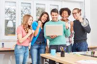 Start-Up Team mit Laptop jubelt über einen Erfolg