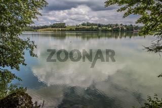 Der Weissensee westlich von Füssen im Landkreis Ostallgäu. Blick vom Wanderweg am südlichen Ufer nach Oberried. Der bewökte Himmel spiegelt sich in der schillernden Wasseroberfläche des Sees.