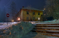 Night shot of street under snow with old residential house in winter season