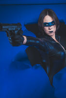Fashion, Brunette girl dressed in leather and latex fitted with pistol on blue background