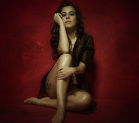Sensual nude brunette woman with long black hair, on red wall with textures