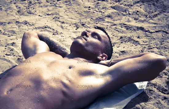 Young Handsome Man Resting On The Sand After A Swim