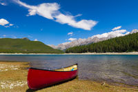 Red Canoe on the shore of a mountain lake