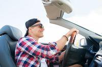 happy young man driving convertible car